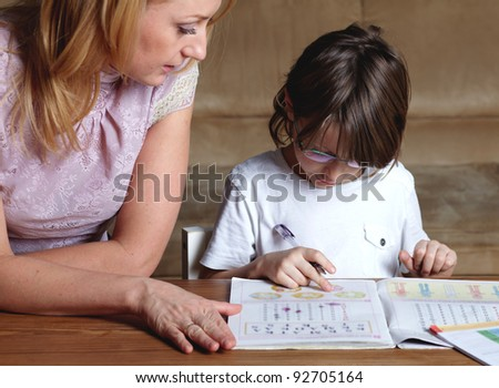 Mother helps her son to do homework - stock photo