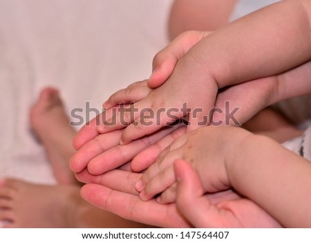 Mother hold baby's hand - stock photo