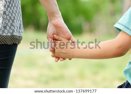 Mother holding a hand of her son - stock photo
