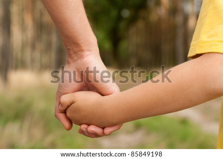 Mother holding a hand of his son in summer day outdoors - stock photo