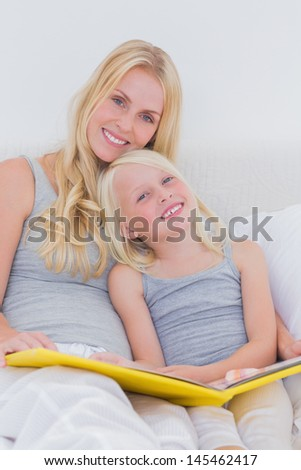 Mother holding a story book with her daughter in bed - stock photo