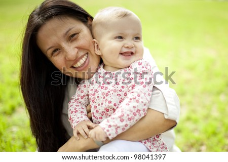 Mother holding Baby Girl at the Park - stock photo