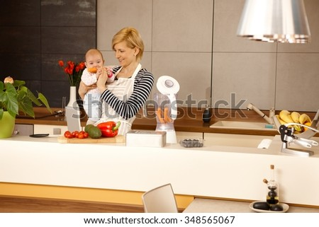 MOther holding baby girl in kitchen. Baby eating carrot. - stock photo