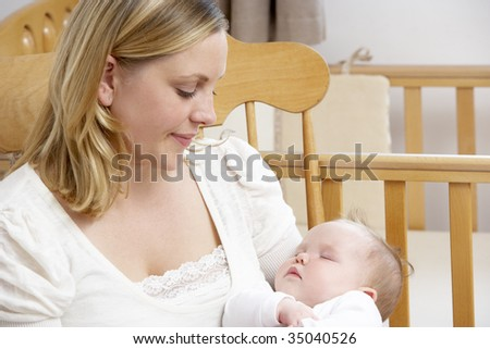 Mother Holding Baby In Nursery - stock photo