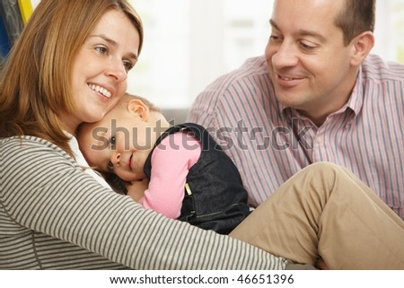 Mother holding cuddling baby girl smiling, father looking at them proudly. - stock photo