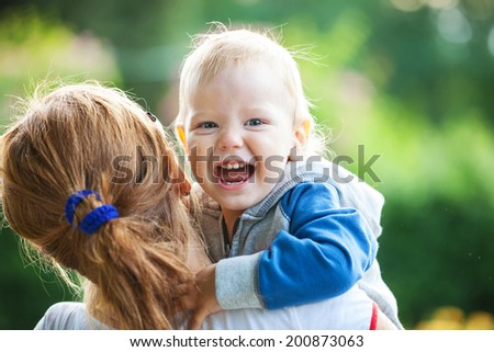 Mother holding happy screaming boy   - stock photo