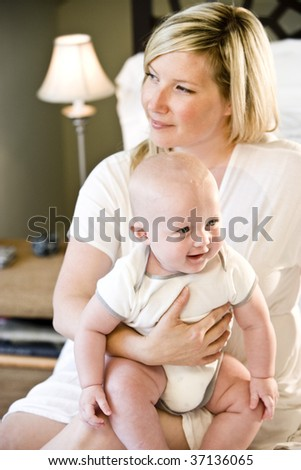 Mother holding happy seven month old baby on her lap - stock photo