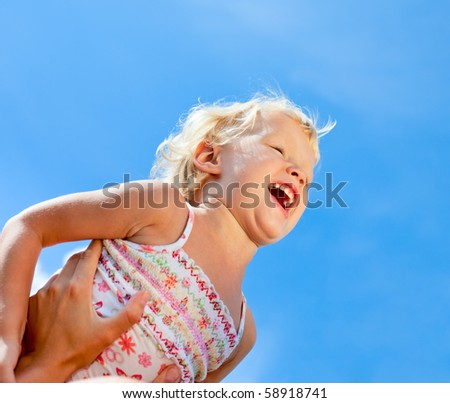 Mother holding her child against blue sky - stock photo