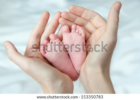 Mother holding her child's feet - stock photo