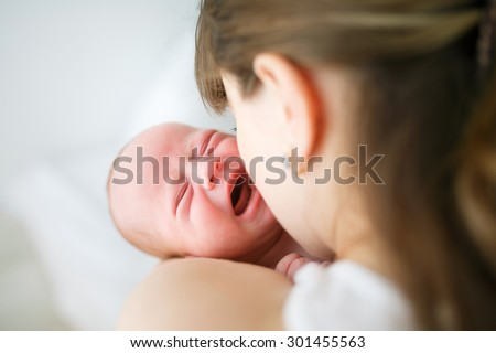 Mother holding her crying little son in studio - stock photo