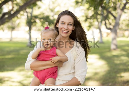 Mother holding her cute little girl in a park - stock photo