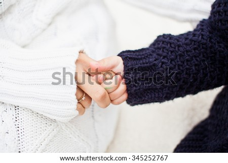 Mother holding her daughter hand. Daughter holding mom's finger. Both in warm and cozy sweaters. Daughter in blue or black sweater and mother in white sweater. Conceptual photo of diversity and family - stock photo