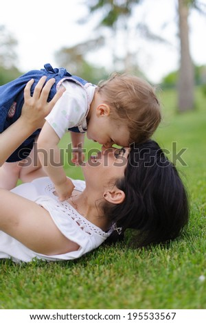 mother holding her daughter in arms and having fun - stock photo