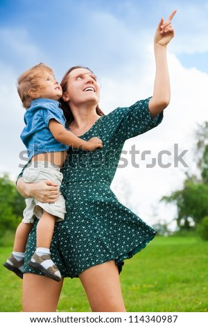 Mother holding her kid and pointing at something - stock photo