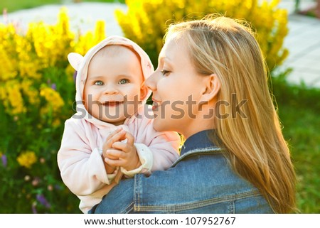 mother holding her little daughter and baby looking at camera outdoors - stock photo