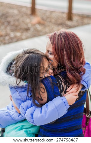 Mother holding her young daughter at a park in Reno, Nevada, USA.  - stock photo