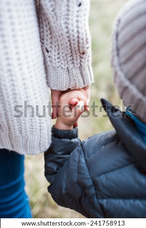 Mother holding his son by a hand - stock photo