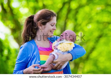 Mother holding newborn baby in a park. Mom playing with her new born son in the garden. Family with kids play outdoors. Young woman hugging little boy. Parents and children having fun in summer. - stock photo