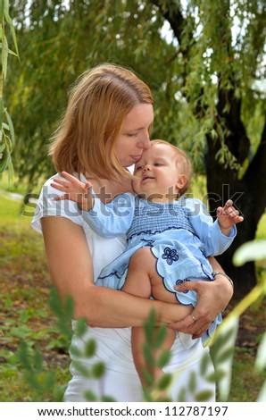 mother holding on hands her sweet baby girl in blue dress in the park - stock photo