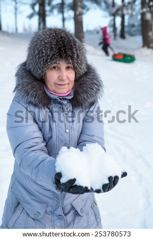 Mother holding snow in hands while child riding with tube on downhill - stock photo