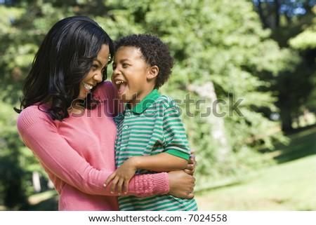 Mother holding young son looking into each other's eyes and smiling. - stock photo