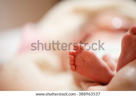 Mother holds in his hands a small baby foots - stock photo