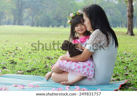 mother hug and kissing her baby in the park - stock photo