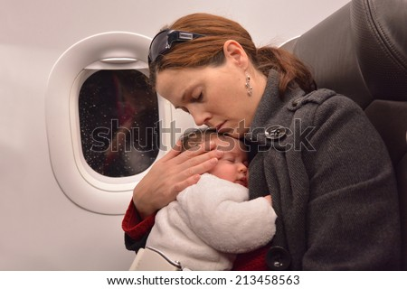 Mother hug and sleep with her newborn baby during flight. Concept photo of air travel with baby. - stock photo