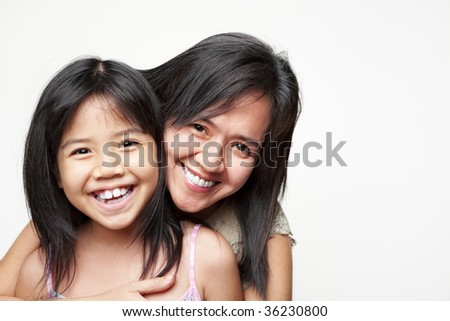 Mother hugging her daughter and posing to camera - stock photo