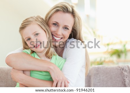 Mother hugging her daughter on the sofa - stock photo