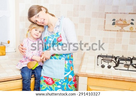 Mother hugging her little daughter in the kitchen. - stock photo