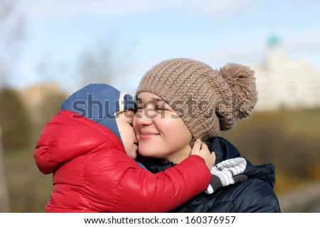 Mother hugging her son at the park in autumn - stock photo
