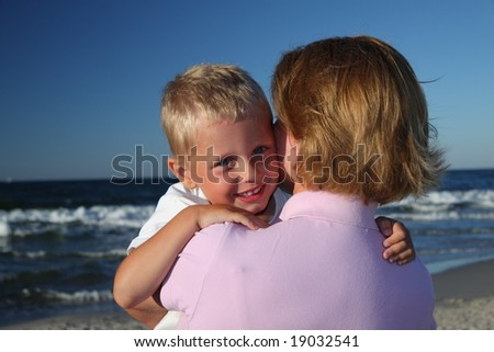 Mother hugging her son on a beach. - stock photo