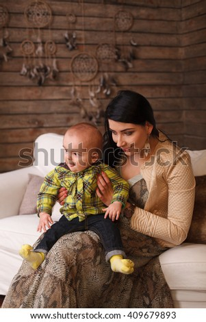 Mother hugging her son, the child poses a funny face. Cute little boy making grimaces - stock photo