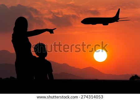 Mother  hugging her son  use hand point airplane on the sky at sunset  - stock photo