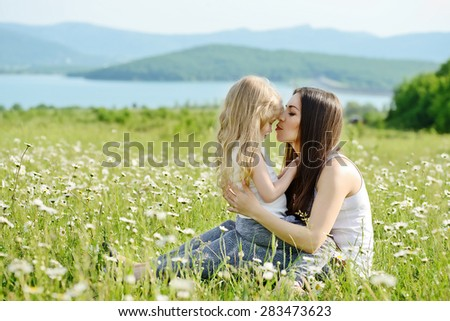 mother hugging with toddler girl in daisy field - stock photo