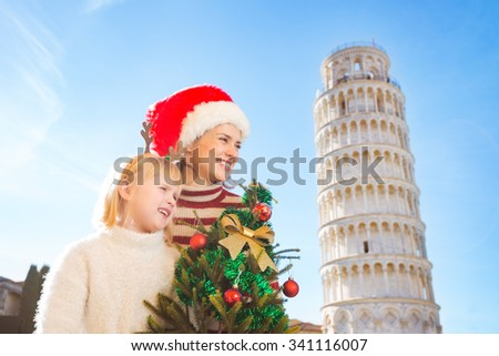 Mother in Christmas hat and daughter in funny reindeer antlers holding Christmas tree looking on copy space in front of Leaning Tour of Pisa, Italy. They spending exciting Christmas time traveling. - stock photo