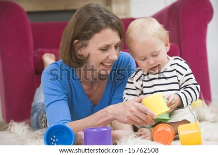 Mother in living room playing with baby smiling - stock photo