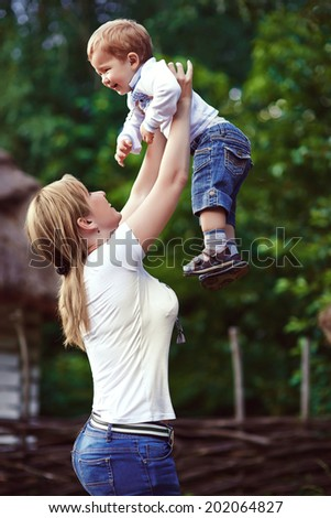 Mother in park playing with her laughing son - stock photo