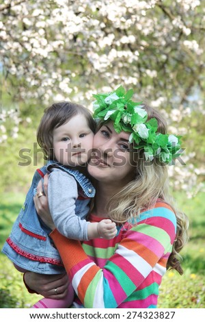 Mother in wreath hugging baby girl under spring tree - stock photo