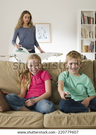 Mother ironing with children watching television at home - stock photo