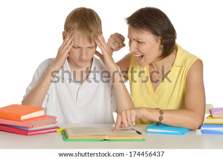 Mother is angry at her son doing homework - stock photo