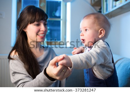 Mother is enjoying time with her little son. Interaction between infant and young woman. Small boy is looking outside with surprised face. Blue cold light from window. Color toned image. - stock photo
