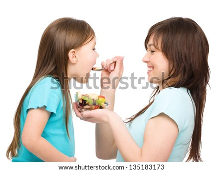 Mother is feeding her daughter with fruit salad, isolated over white - stock photo