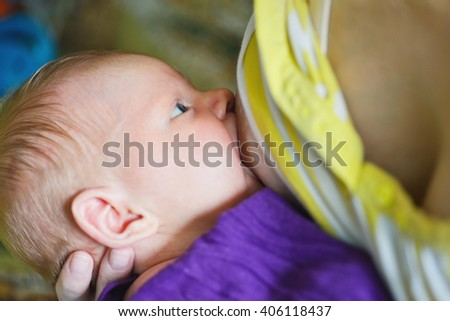 mother is feeding her newborn with breast - stock photo