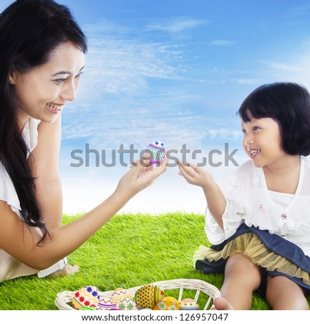 Mother is giving an easter egg to her daughter outdoor, under blue sky - stock photo