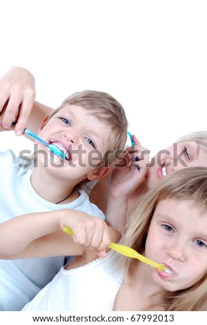 Mother is helping her son to brush his teeth well.Shallow depth of field. The focus is on the boy's face. - stock photo