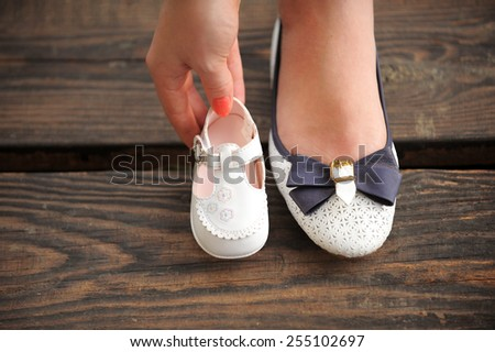 mother is holding child's shoe close to her own - stock photo