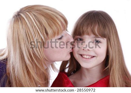 Mother is kissing her happy daughter. Mother's kiss. Isolated on white in studio. - stock photo