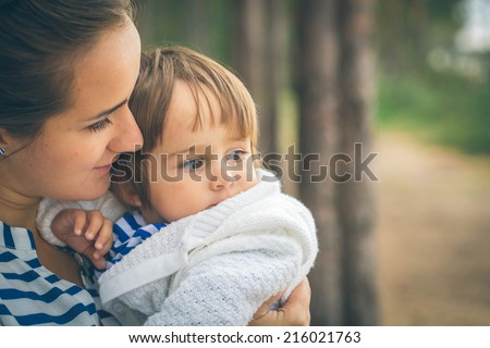 mother is playing with child on nature - stock photo